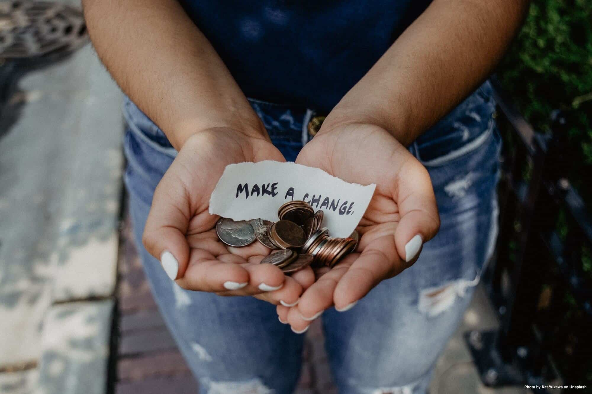 women holding coins to show making change through charity and justice
